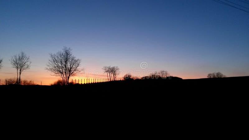 Сельский голубой оранжевый заход солнца стоковые фотографии rf