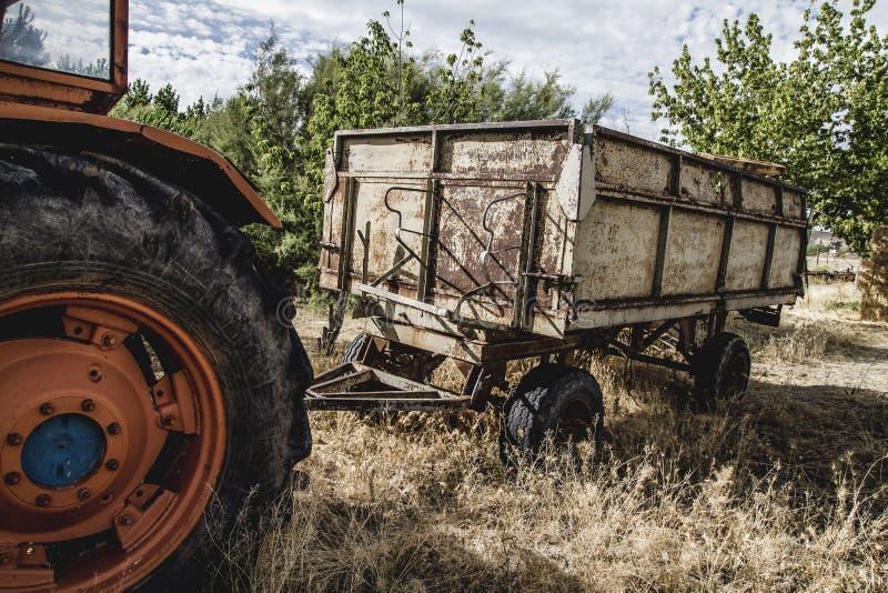 сельский, старый аграрный трактор покинутый в поле фермы стоковые изображения
