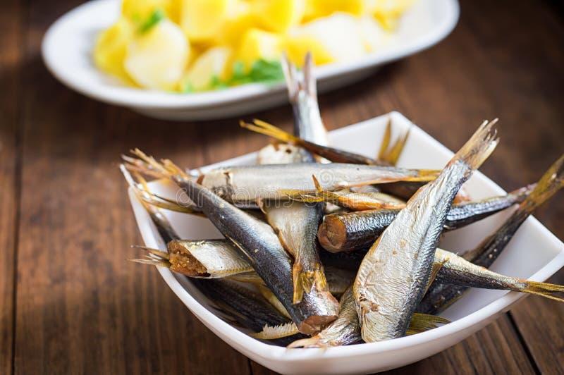 Сельди малых копченых рыб прибалтийские с кипеть картошками Деревянная предпосылка Конец-вверх Взгляд сверху стоковые изображения