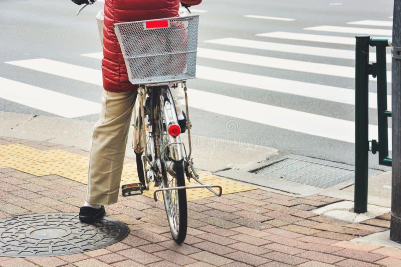 Сзади женщины на старинном велосипеде ждут на тротуаре, чтобы пересечь дорогу на перекрестке стоковые изображения rf