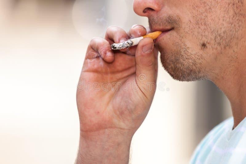 Сигарета взрослого человека куря снаружи стоковое фото rf