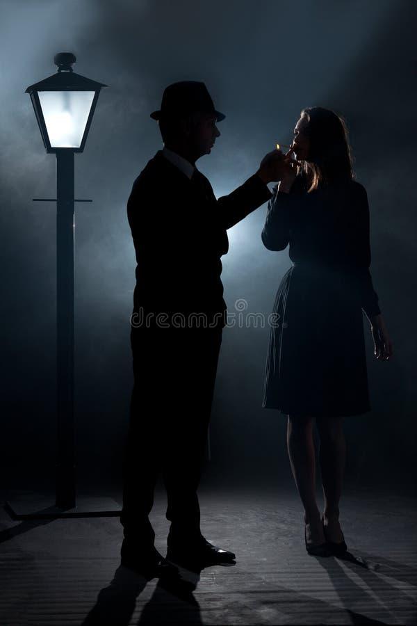 Сигарета освещения тумана фонарного столба пар фильма noir стоковые фотографии rf