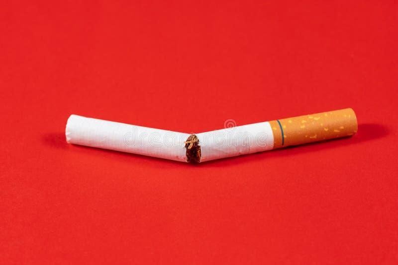 Сигарета табака сломанная близко вверх с красной предпосылкой стоковые фото