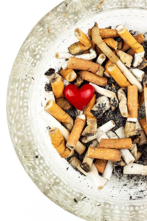 Сигареты в стеклянном ashtray на белой предпосылке Обработка рака легких Табачная промышленность стоковые фотографии rf