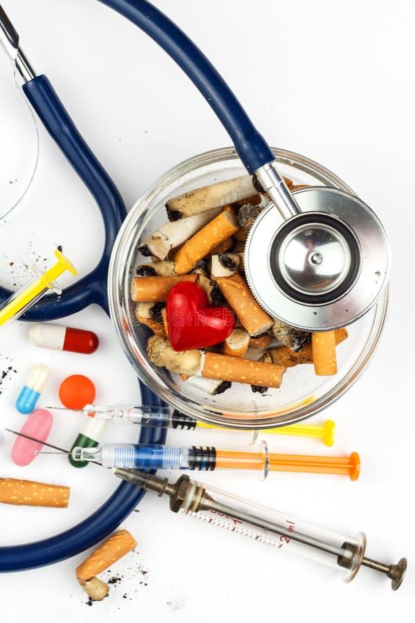 Сигареты в стеклянном ashtray на белой предпосылке Обработка рака легких Стетоскоп и лекарство стоковое изображение
