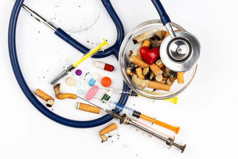 Сигареты в стеклянном ashtray на белой предпосылке Обработка рака легких Стетоскоп и лекарство стоковые изображения rf