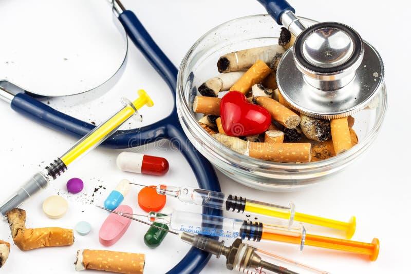 Сигареты в стеклянном ashtray на белой предпосылке Обработка рака легких Стетоскоп и лекарство стоковая фотография rf