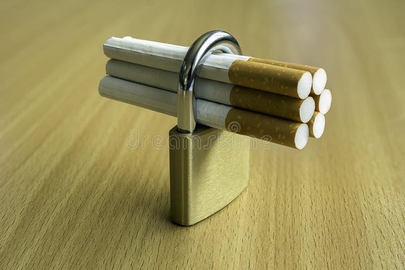 Сигареты в keylock на деревянной предпосылке стоковое изображение