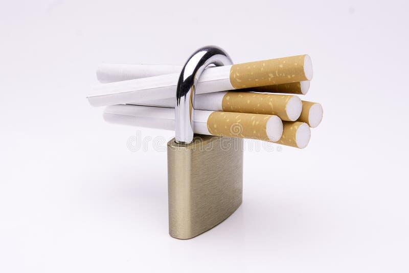 Сигареты запертые с padlock на белой предпосылке стоковые изображения