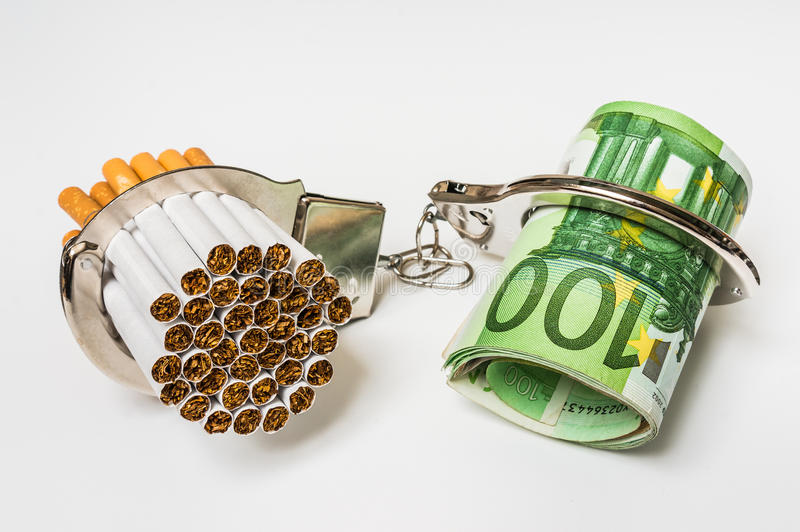 Сигареты и деньги с наручниками - цена курить стоковые фотографии rf