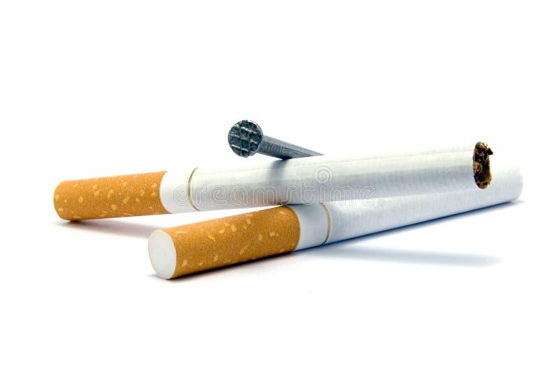 Сигареты и метафора ногтя гроба, злоупотребление и прекращенный курить крупный план макроса концепции большой детальный изолирова стоковые изображения rf