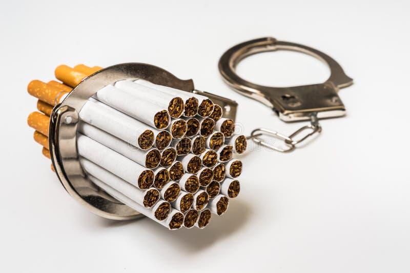 Сигареты и наручники - куря концепция наркомании стоковая фотография