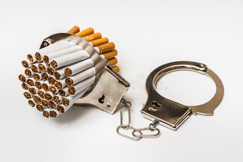Сигареты и наручники - куря концепция наркомании стоковое изображение rf