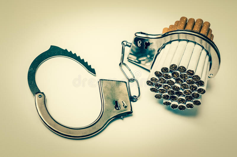 Сигареты и наручники - куря концепция наркомании стоковые фото