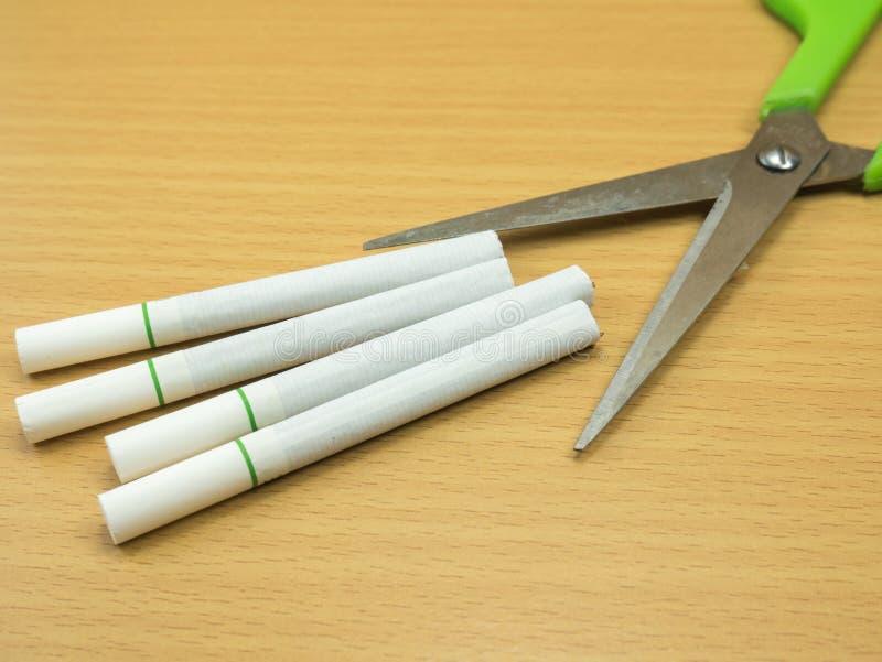Сигареты на деревянной предпосылке с концепцией ножниц останавливают дым стоковое изображение