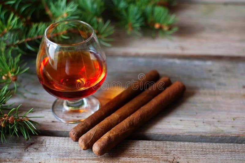 Сигары и коньяк на старом деревянном столе стоковые фотографии rf
