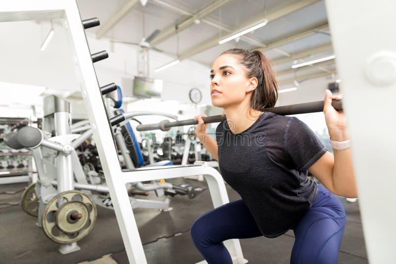 Сидение на корточках штанги подходящей женщины практикуя в фитнес-клубе стоковая фотография