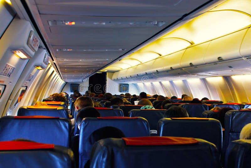 Сиденье пассажира, интерьер самолета при пассажиры сидя на местах стоковые фотографии rf