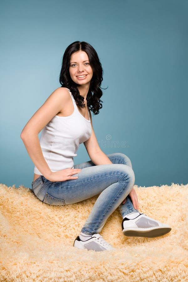 сидеть джинсыов девушки кресла стоковая фотография rf