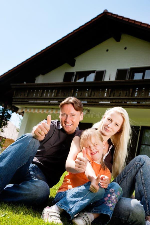 сидеть дома семьи передний их стоковое фото rf