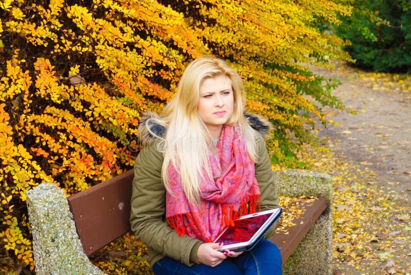 Сидеть женщины ослабляя на стенде в парке используя таблетку стоковые фотографии rf