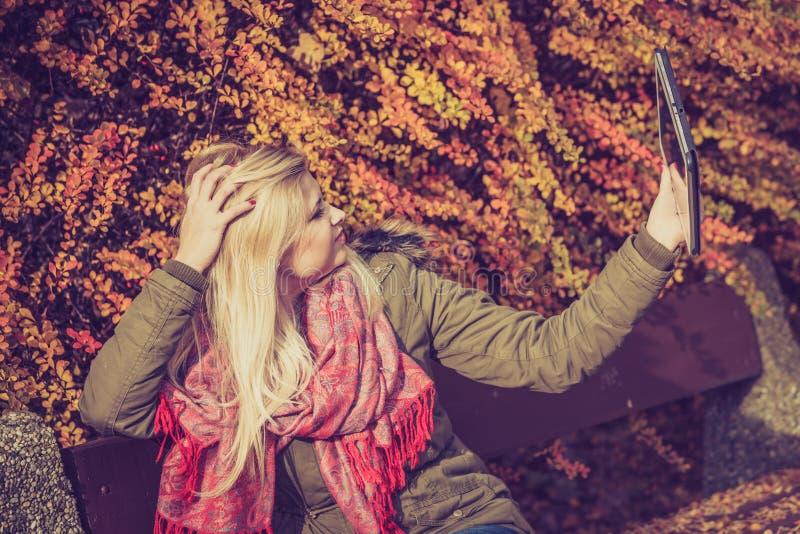 Сидеть женщины ослабляя на стенде в парке используя таблетку стоковое фото