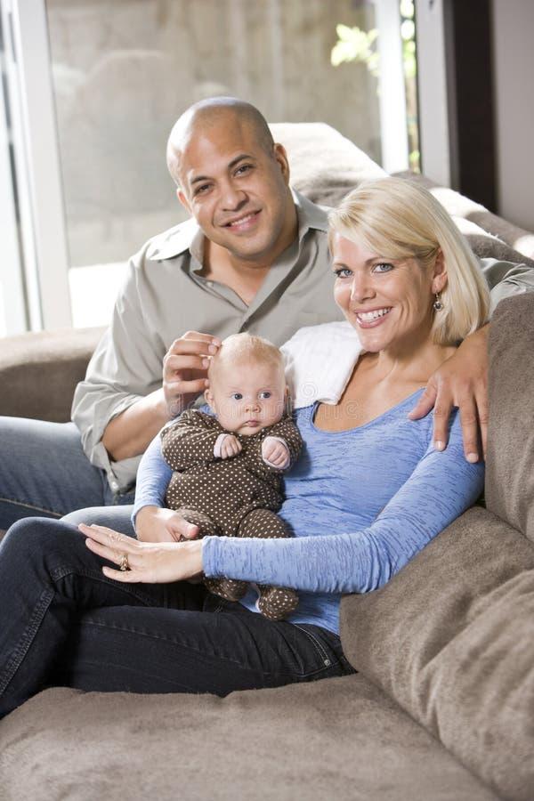 сидеть любящих родителей внапуска дома младенца стоковые фото