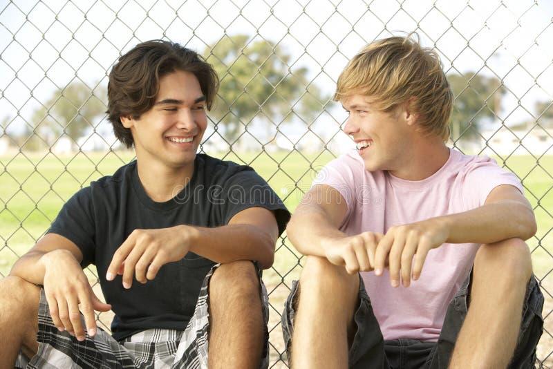 сидеть спортивной площадки мальчиков подростковый стоковое изображение rf