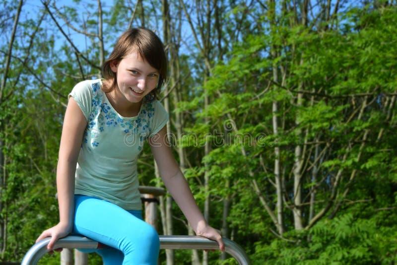 Сидеть счастливого девочка-подростка усмехаясь на трубе металла в парке стоковое изображение rf