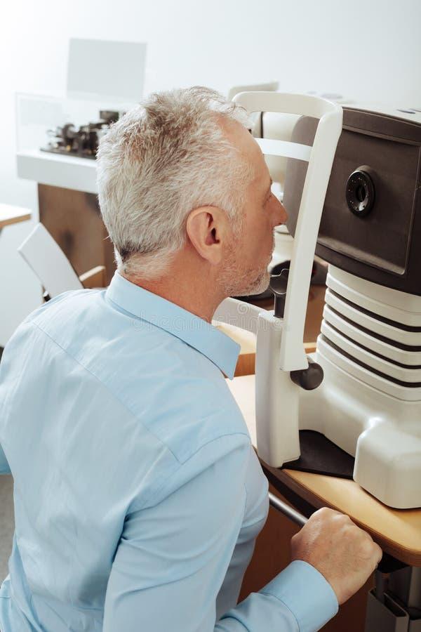 Сидеть человека прямой пока имеющ анализ вздоха глаза стоковое изображение rf