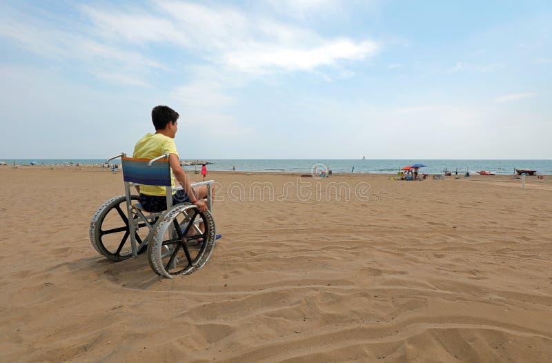 Сидящий в инвалидной коляске мальчик-инвалид смотрит на море стоковые фото