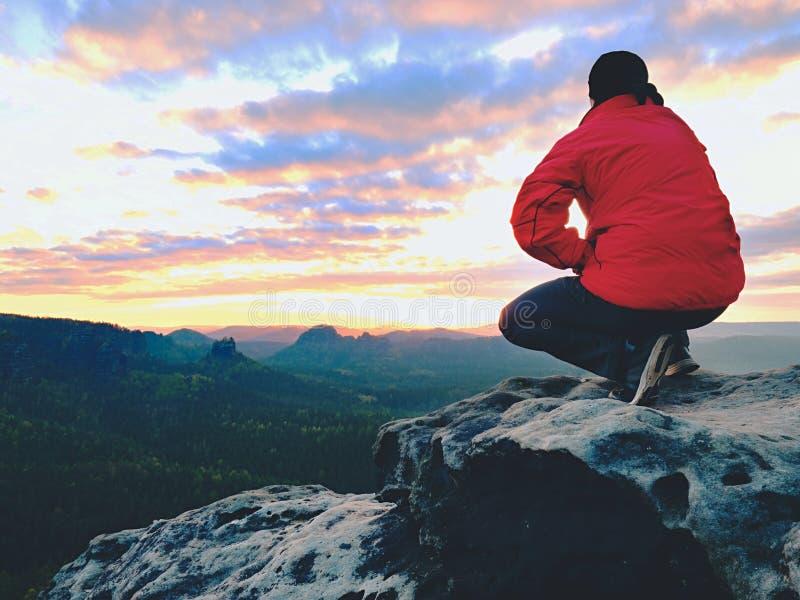Сидя hiker на утесе Человек в красных черных теплых одеждах сидит на скале и наслаждается далеким взглядом стоковая фотография rf