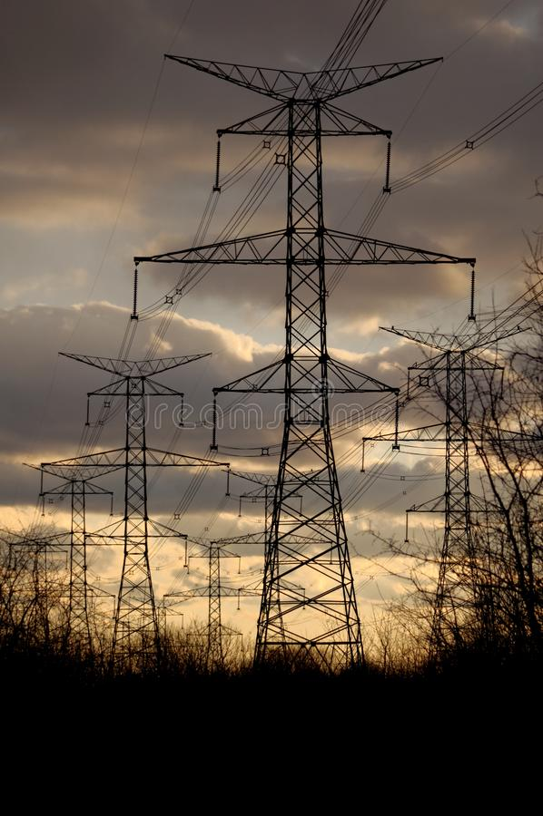 Сила - опоры и линии электричества на заходе солнца стоковая фотография rf