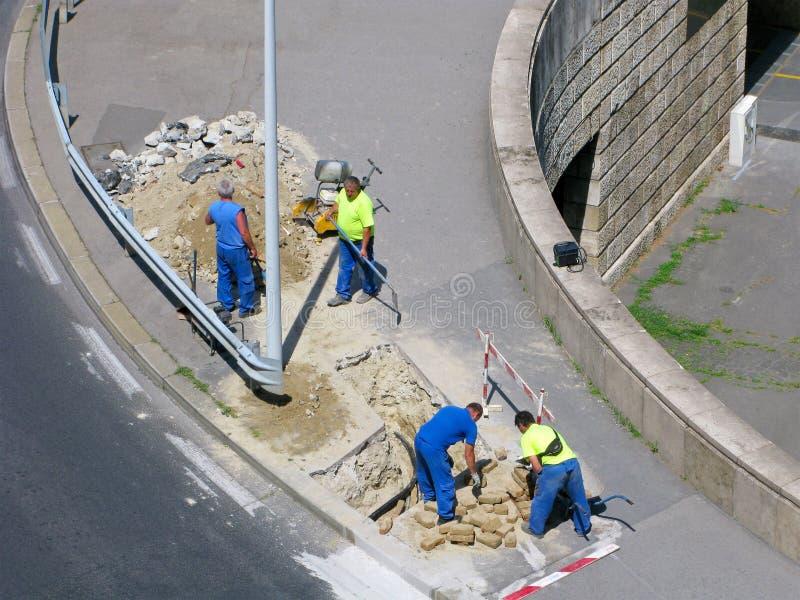 Силовой кабель кладя, группа в составе построители, городская улица, взгляд сверху стоковые фото