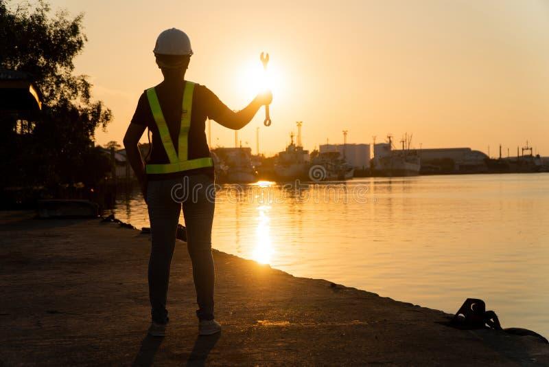 Силуэты азиатского инженера женщины держа ключи и стоя на верфи и предпосылке силосохранилище нефтехранилища Концепция женщин стоковое фото rf