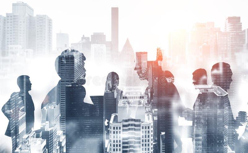 Силуэты бизнесменов в сером городе стоковое изображение rf