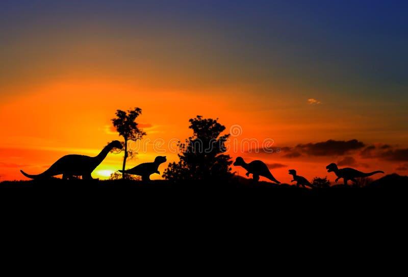 Силуэты динозавров в лесе на предпосылке захода солнца с космосом экземпляра стоковое фото rf