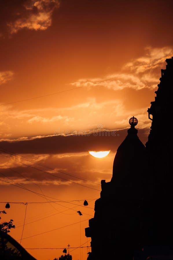 Силуэты захода солнца города стоковые изображения