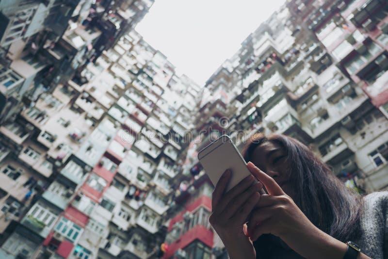 Силуэты и изображение низкого угла женщины используя мобильный телефон с толпить жилым домом в общине в заливе карьера стоковые изображения rf