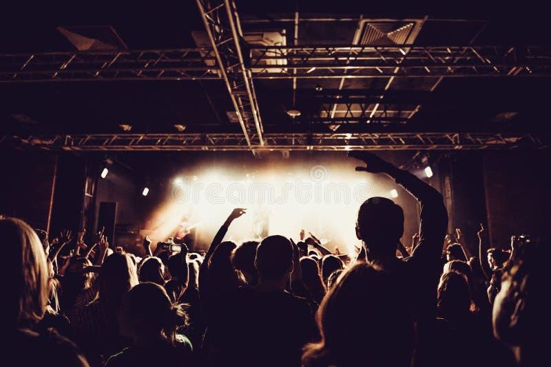 Силуэты концерта толпятся перед яркими светами этапа веселя толпа людей с руками вверх на популярном концерте рок-музыки стоковое фото