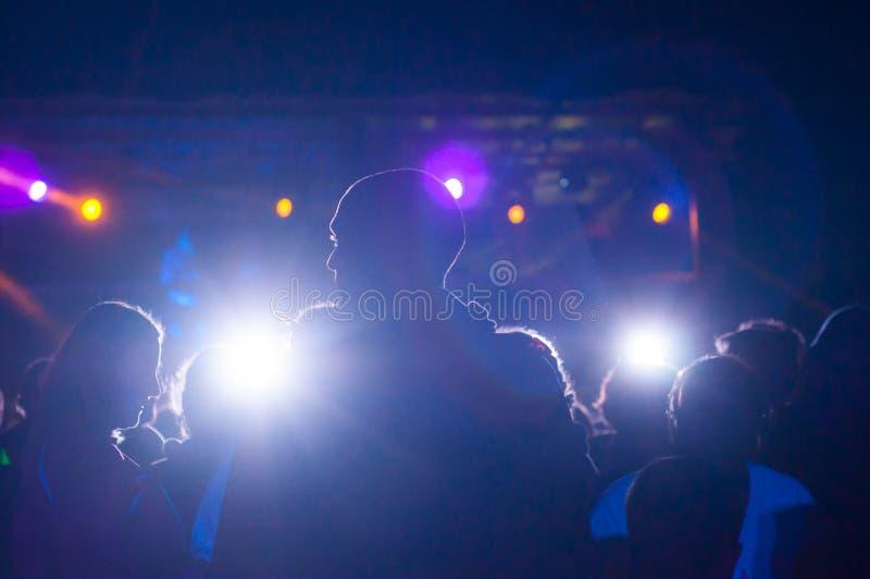 Силуэты людей в ночном клубе с светами стоковые фотографии rf