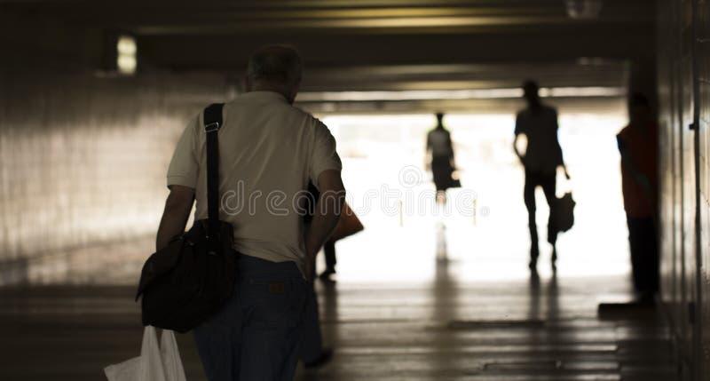 Силуэты людей идя в темный тоннель против белого зарева стоковые изображения rf