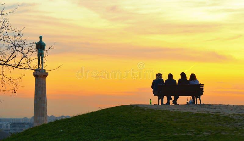 Силуэты людей на теплом красочном заходе солнца в Белграде, Сербии стоковое изображение