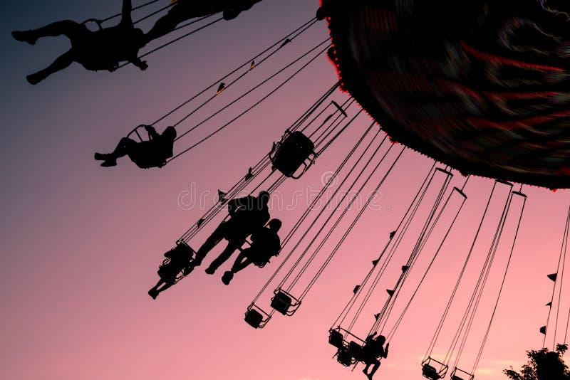 Силуэты людей на carousel качания против фиолетового неба вечера стоковая фотография