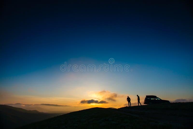 Силуэты 2 людей стоя на горе покрывают стоковая фотография rf