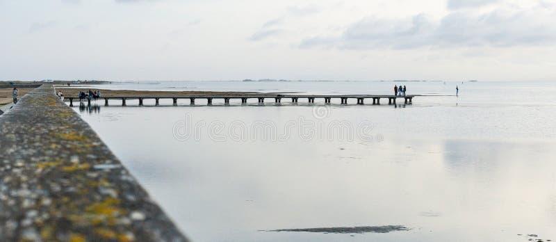 Силуэты непознаваемых людей на пристани на заходе солнца стоковые фото
