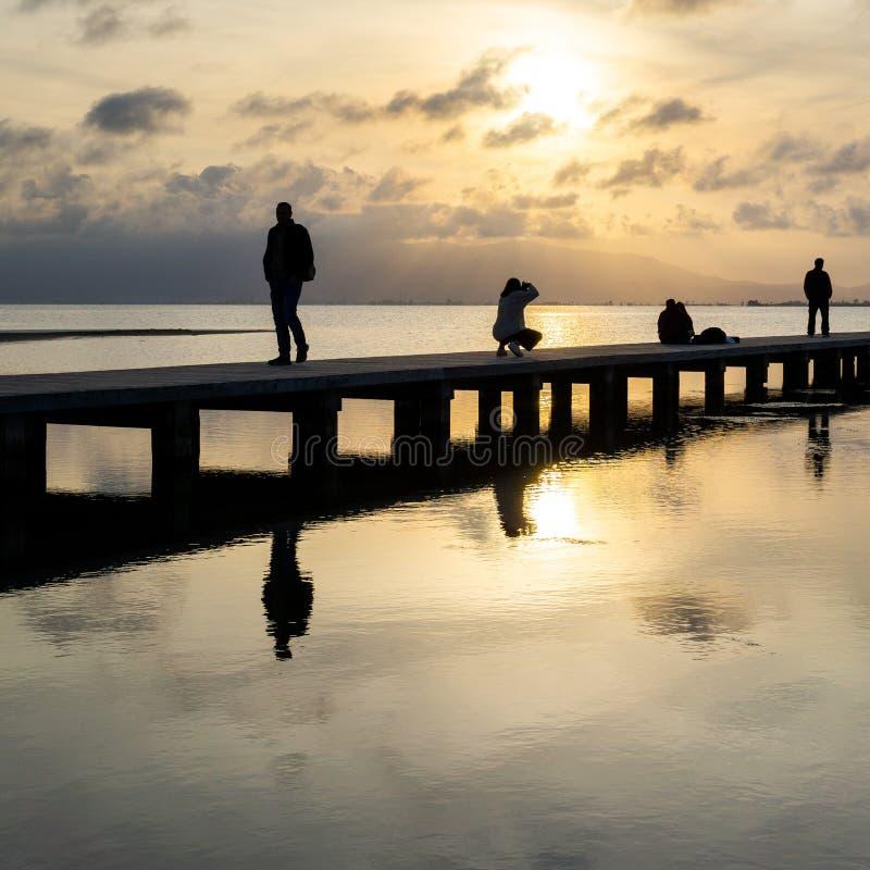 Силуэты непознаваемых людей на пристани на заходе солнца стоковые изображения rf
