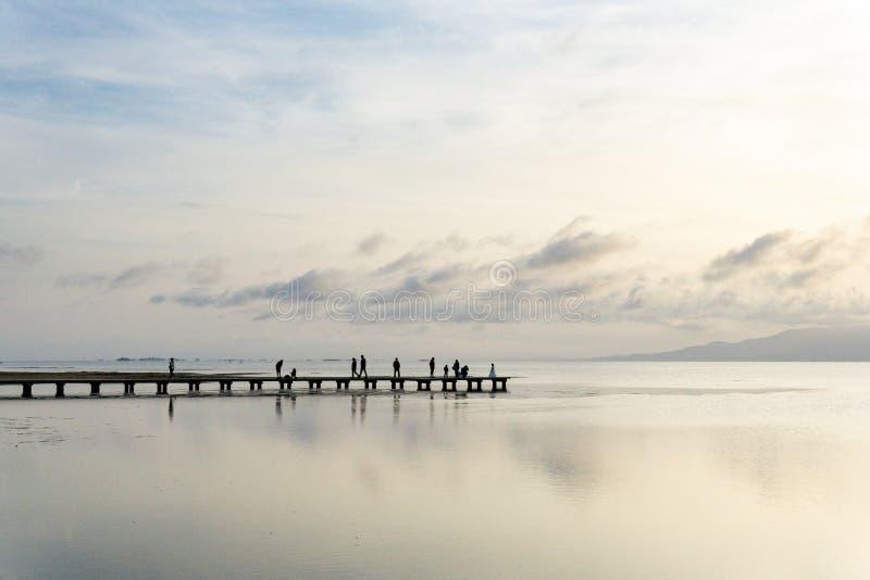 Силуэты непознаваемых людей на пристани на заходе солнца стоковое изображение rf