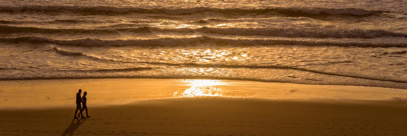 Силуэты пары наслаждаясь заходом солнца на Атлантическом океане Lacanau Франции стоковая фотография