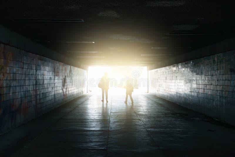 Силуэты прогулки женщины и ребенк, который нужно осветить в конце подземного тоннеля стоковая фотография